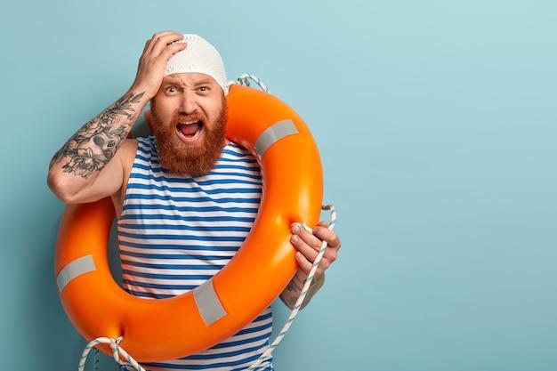 Gefrustreerde professionele mannelijke redder schreeuwt van wanhoop, houdt de hand op het hoofd, schrikt het risico om te verdrinken, gebruikt een speciale opgeblazen reddingsboei