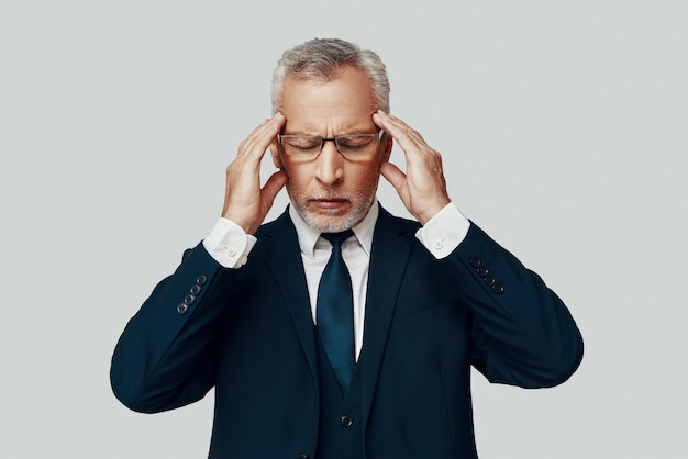 Gefrustreerde senior man in volledig pak die lijdt aan hoofdpijn terwijl hij tegen een grijze achtergrond staat