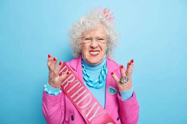 Gefrustreerde senior vrouw steekt handen op en kijkt met spijt, verjaardagsconcept