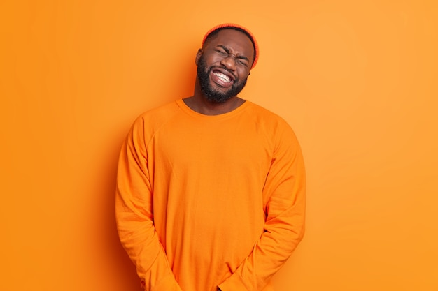 Gefrustreerde sombere bebaarde volwassen man kantelt hoofd klemt tanden probeert zijn slechte emoties te beheersen voelt zich erg ongelukkig huilt van wanhoop draagt hoed casual trui geïsoleerd over oranje muur