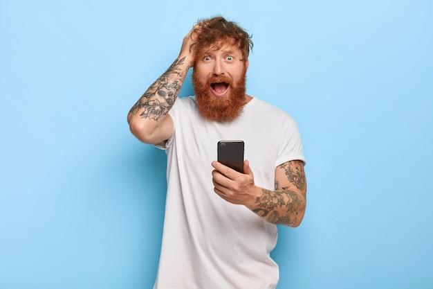 Gefrustreerde stressvolle gember hipster houdt de hand op het hoofd, kijkt met bezorgde gezichtsuitdrukking, opent de mond, houdt moderne mobiele telefoons vast, voelt angst door een fout te maken, heeft iets verkeerd gedaan met de app