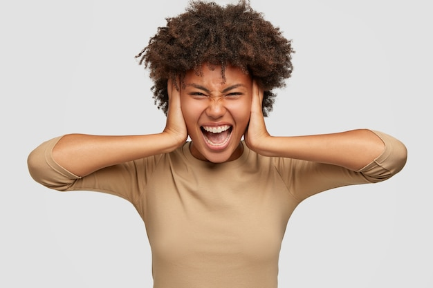 Gefrustreerde stressvolle zwarte dame bedekt oren met beide handen, fronsend gezicht