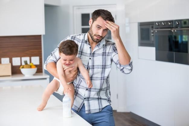 Gefrustreerde vader die huilende babyjongen houdt