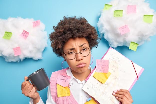 Gefrustreerde, verdrietige afro-amerikaanse student heeft een vermoeide uitdrukking voelt zich slaperig nadat hij de hele dag voor het examen heeft geprepareerd, omringd door geplakte stickers, maakt aantekeningen op papier om informatie te onthouden drinkt koffie