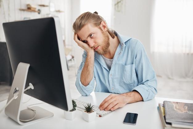 Gefrustreerde, vermoeide, bebaarde blanke werknemer die zijn hoofd aanraakt, zich absoluut uitgeput voelt vanwege overwerk, rekeningen berekenen, achter een computerscherm zit. deadline en overwerk