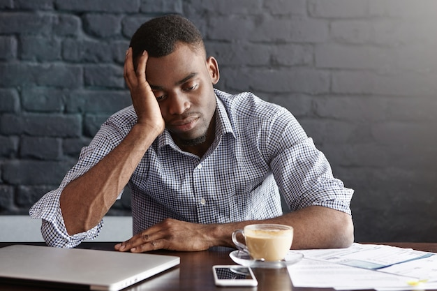 Gefrustreerde vermoeide jonge afro-amerikaanse werknemer raakt zijn hoofd aan