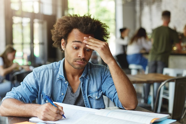 Gefrustreerde verwarde jonge student met afro-kapsel die voorhoofd wrijft, hard probeert ingewikkelde wiskundige problemen te begrijpen terwijl hij huiswerk maakt in café, pen gebruikt om aantekeningen te maken