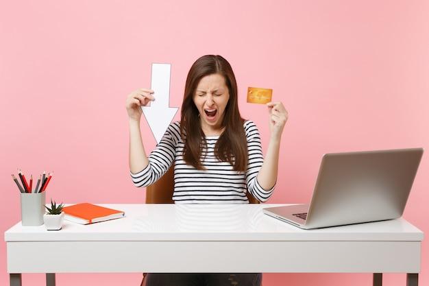 Gefrustreerde vrouw die schreeuwt terwijl ze de waarde van de valpijl-creditcard ingedrukt houdt, zit en werkt aan een wit bureau met een moderne pc-laptop