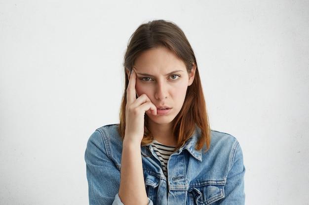 Gefrustreerde vrouw houdt vinger op tempel, probeert zich te concentreren op haar werk, maar voelt zich vermoeid, kijkt met vermoeide uitgeputte uitdrukking