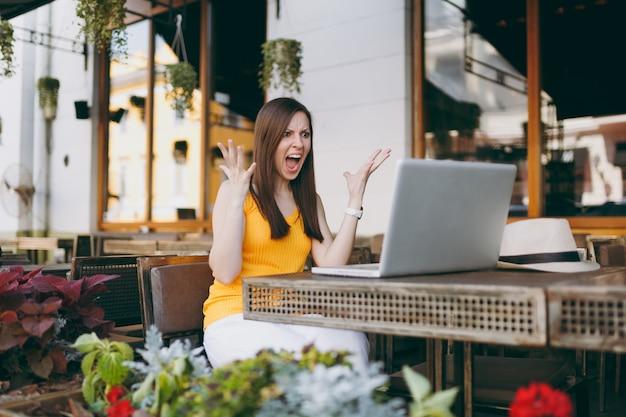 Gefrustreerde vrouw in de buitenlucht in een straatcafé, zittend aan tafel met een moderne laptop-pc-computer, terwijl ze in de vrije tijd handenrestaurant verspreidt