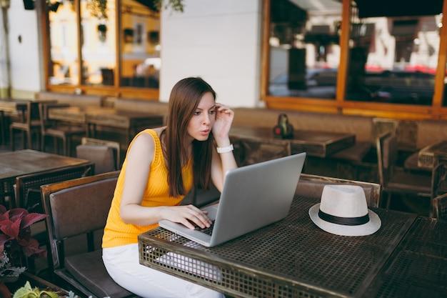 Gefrustreerde vrouw in de buitenlucht, straatcafé, zittend aan tafel, werkend op moderne laptop-pc, restaurant in vrije tijd