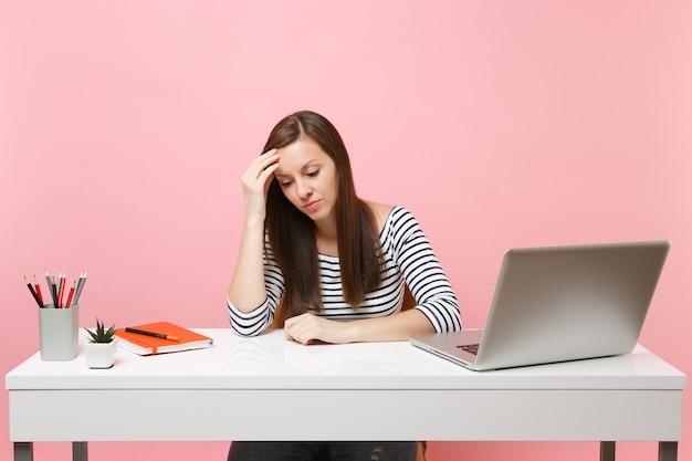 Gefrustreerde vrouw in wanhoop die op de hand leunt en neerkijkt, zit, werkt aan een wit bureau met een moderne pc-laptop