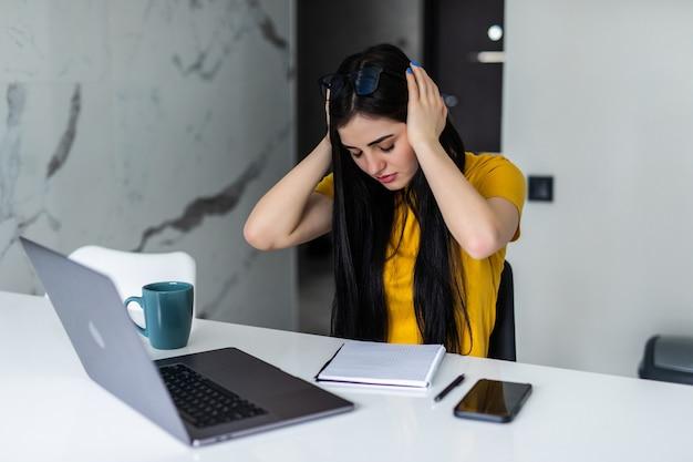 Gefrustreerde vrouw werkt vanuit huis op haar laptop en houdt haar hoofd thuis in de keuken