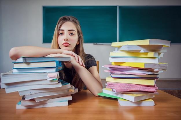 Gefrustreerde vrouwelijke student zit aan de balie met een enorme stapel studieboeken in de klas