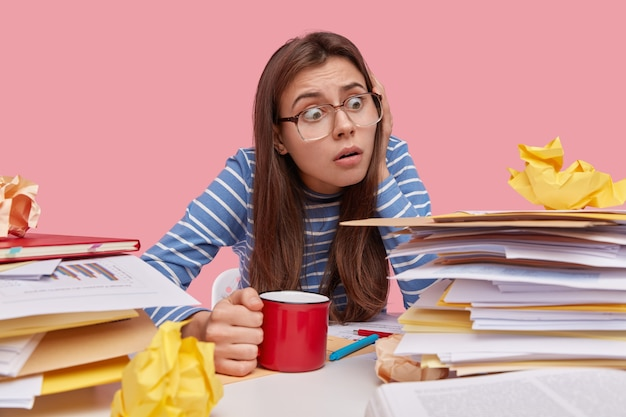 Gefrustreerde vrouwelijke werkgever poseert op het werk, heeft angstige uitdrukking, schrik van het werken met documentatie, drinkt warme dranken