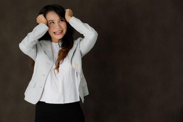 Gefrustreerde wanhopige jonge aziatische vrouw in elegante kleding met gesloten ogen, handen op het hoofd houdend en huilend terwijl ze problemen krijgen tegen een donkergrijze achtergrond