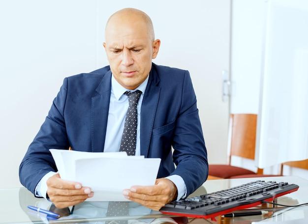 Gefrustreerde zakenman aan het werk op kantoor interieur