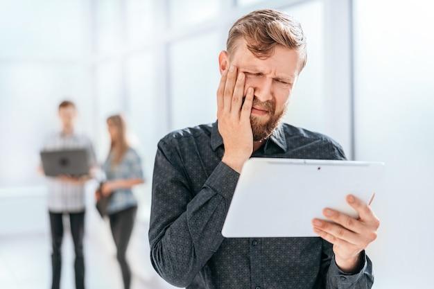 Gefrustreerde zakenman die het scherm van zijn tablet bekijkt