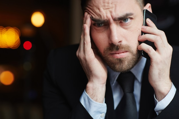Gefrustreerde zakenman die op telefoon spreekt
