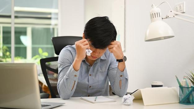 Gefrustreerde zakenman op zoek naar informatie over papierwerk en verfrommeld papier.