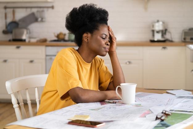Gefrustreerde zwarte zakenvrouw die zich zorgen maakt over een probleem, zit in de keuken, thuiswerk lijdt aan hoofdpijn