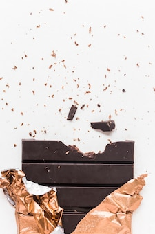 Gegeten donkere chocoladereep in gouden omslag op witte achtergrond