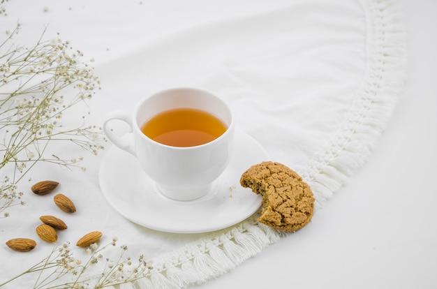 Gegeten koekjes en amandelen met witte kruidentheekop op tafelkleed