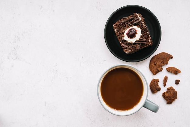 Gegeten koekjes; plakje cake en koffiekopje op witte achtergrond