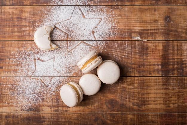 Gegeten maanvorm bitterkoekjes met stervorm op suikerpoeder over het houten oppervlak