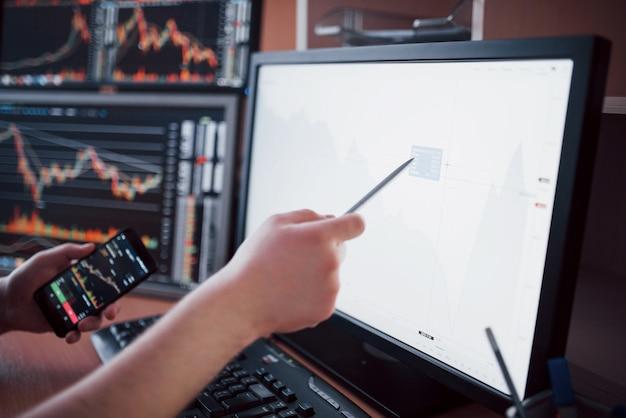 Gegevens analyseren. close-up van jonge zakenman die op de gegevens richten die in de grafiek met pen worden voorgesteld terwijl het werken in creatief bureau