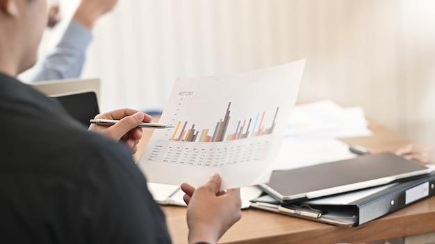 Gegevens van de analyse statische financiën van de close-upzakenman in vergaderzaal.