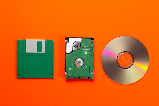 Gegevensopslagmedium evolutie - floppy disk, cd-schijf, kleine harde schijf op oranje achtergrond.