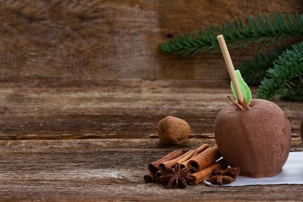 Geglazuurd in chocolade appel voor kerstmis op tafel met kopieerruimte