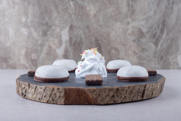 Geglazuurde biscuit en chocoladewafel aan boord op marmeren tafel.