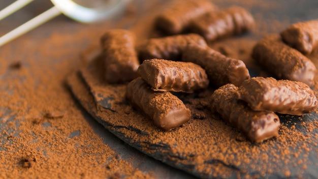 Geglazuurde chocoladekoekjes bedekt met cacaopoeder op zwarte plaat