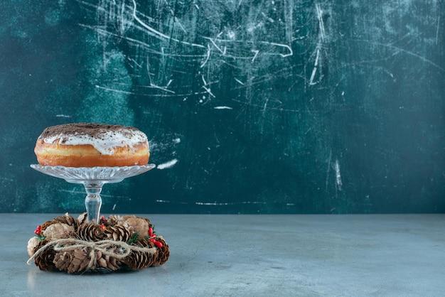 Geglazuurde donut op een glazen sokkel in het midden van een dennenkrans op marmer.