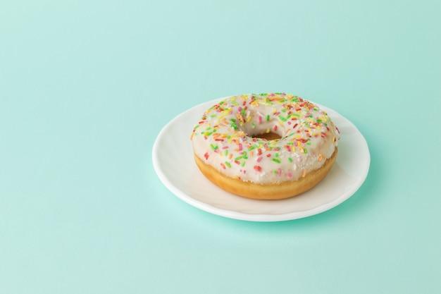 Geglazuurde donut op een witte plaat op een blauw oppervlak