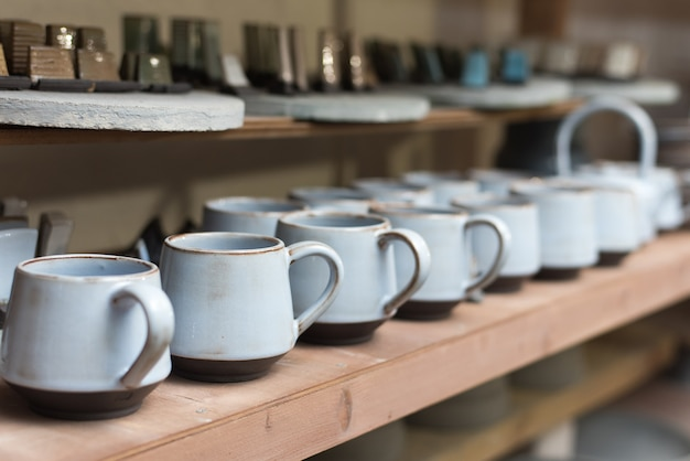 Geglazuurde keramische schalen staan op een plank in de werkplaats met handgemaakte keramische en kleimokken