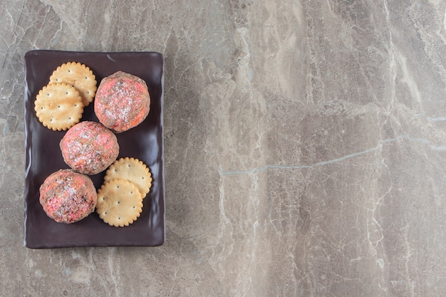 Geglazuurde koekjes en cracker op een schotel op marmer.