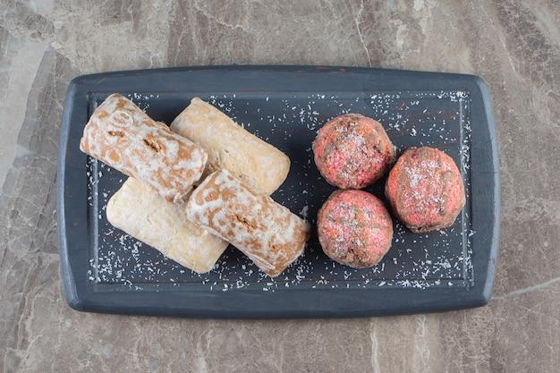 Geglazuurde koekjes en peperkoeken op een dienblad op marmer.