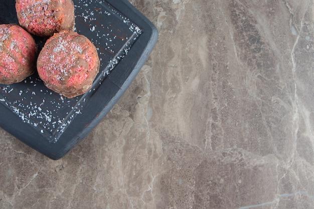 Geglazuurde koekjes op een dienblad op marmer.