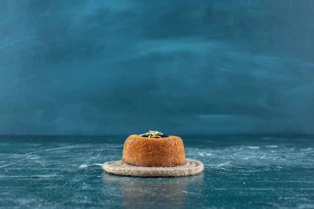 Geglazuurde minicake op een onderzetter, op de blauwe achtergrond. hoge kwaliteit foto