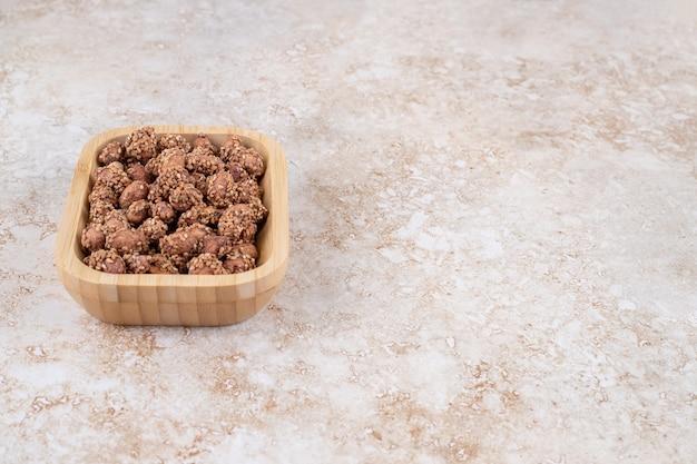 Geglazuurde pinda met sesam op een houten dienblad, op de marmeren tafel.