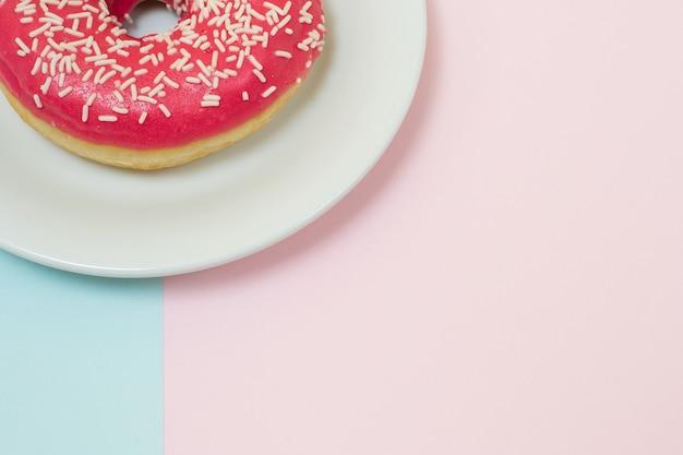 Geglazuurde roze doughnut op plaat tweekleurige pastelblauwe en pastelroze achtergrond