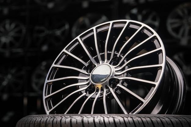 Gegoten aluminium wielen in de winkel. dunne spaken, mooie zwarte kleur en donkere achtergrond.