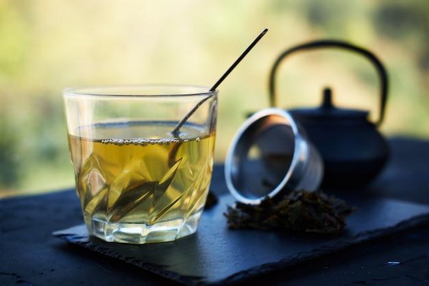 Gegoten groene thee in glazen beker