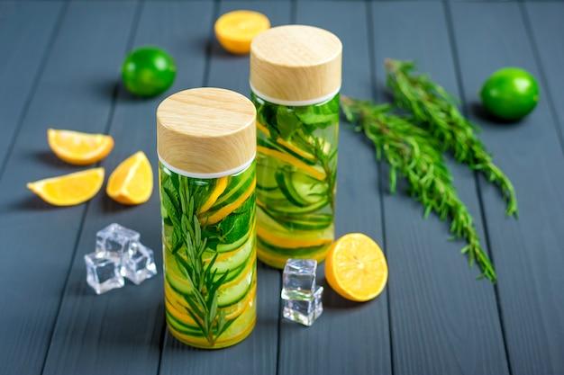 Gegoten water, cocktail, limonade of thee. zomer ijskoud drankje met citroen, dragon, limoen, komkommer en lef van mint op donkergrijze achtergrond.