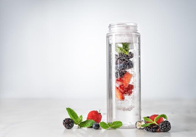 Gegoten water in plastic fles met bessen