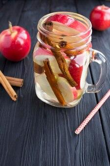Gegoten water met appel en kaneel in het glas op zwarte lijst
