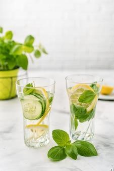 Gegoten water met citroen, cucmber en basilicum op wit